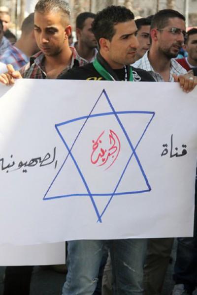 بالصور نشطاء فتح غاضبون برام الله يحاولون اقتحام مكتب قناة الجزيرة 3909988685