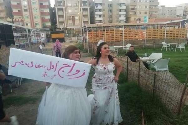 """صور لفتاتين بفستانى زفاف ترفعان لافتة كتب عليها """"زواج أول بنتين فى مصر"""""""