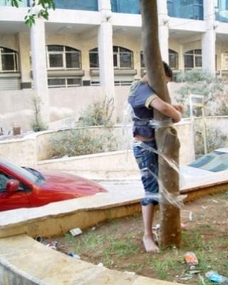 أب يعاقب ابنه ويربطه بشجرة لسرقته علبة كولا