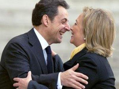 صور وفيديو فضيحة هيلاري كلينتون .. ساركوزي يستقبلها بالقبلات والضرب على المؤخرة