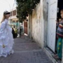مصور إسرائيلي يلتقط صورة لفتاة يهودية في عيد المساخر وهي تبصق على طفل فلسطيني