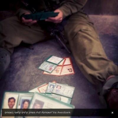 """بالصورة... جنود الاحتلال يلعبون الشدة بـ""""هويات"""" المواطنين"""