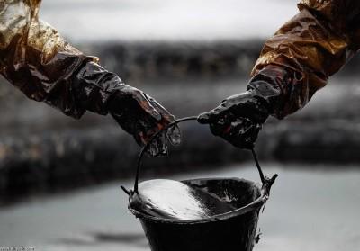 عمال تيلندين يقومون بتنظيف احد البقع النفطية علي احد الشواطئ