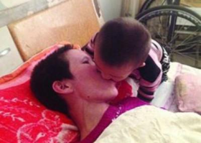 شاهد بالصور.. طفل يمضغ الطعام ليضعه في فم أمه المشلولة
