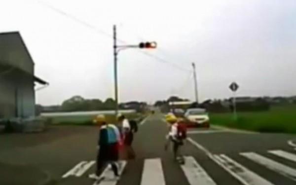 أطفال يؤدون حركة احترام لسيارتين بعد قطعهم للطريق