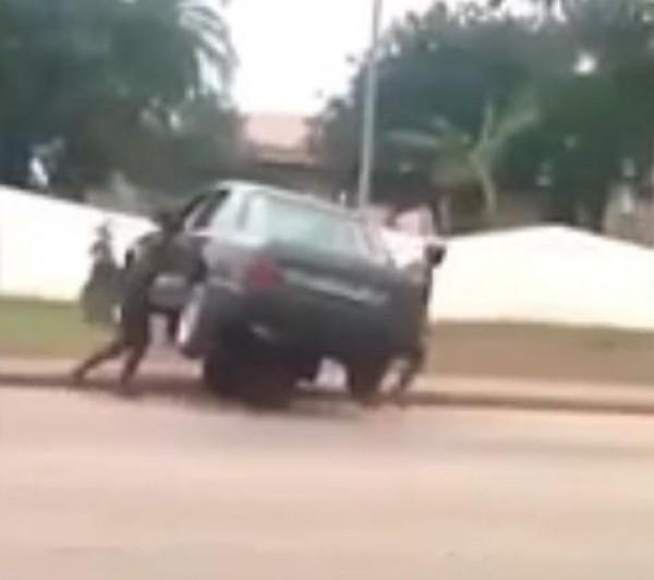 شخصان يحملان سيارة كبيرة فوق عربة