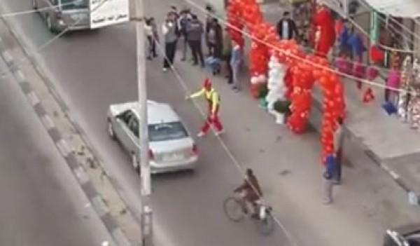 مُهرج يفاجيء السائقين والمارة غرب غزة (فيديو)