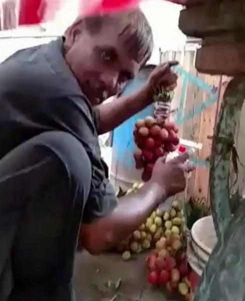 مشهد مرعب لبائع فاكهة يرش العنب باللون الأحمر