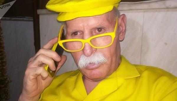"""يرتديه منذ 35 عامًا مستنداً لآية قرآنية.. تعرف على السوري """"الرجل الأصفر"""""""