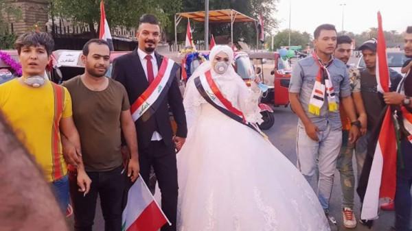 شاهد كيف احتفل عروسيين عراقيين بزفافهما وسط المتظاهرين