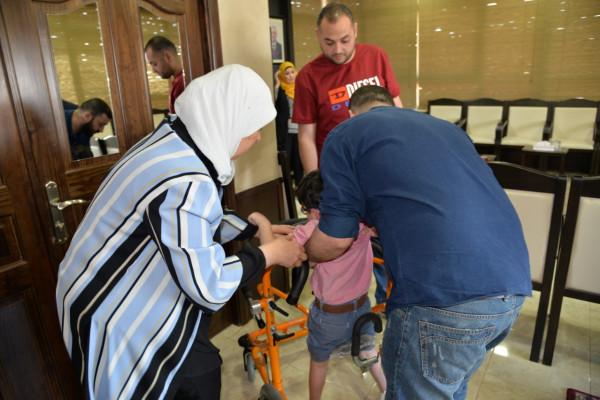 غنام تسلم طفل من ذوي الاحتياجات الخاصة جهازاً لمساعدته على الحركة