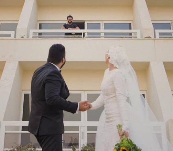 شاهد: بعد إعلان إصابته بـ(كورونا).. عروسان يحظيان (بفوتوسيشن) أمام مكان عزل محمد صلاح