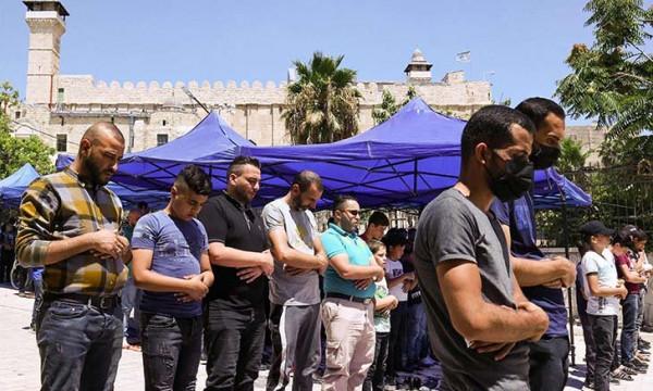 مواطنون يؤدون صلاة الجمعة وسط الخليل