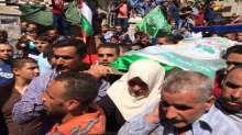 بالصور ..والدة الشهيد عامر ابو عيشه تحمل نعش نجلها الشهيد اثناء مسيرة التشييع بالخليل
