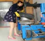 فتاة صينية تعمل في إصلاح عجلات السيارات